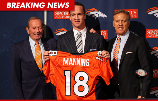 Peyton Manning holds his jersey. He is officially a Denver Bronco.